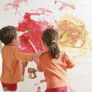 Kinder die eine weiße Wand beschmieren